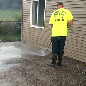 man power washing concrete of house
